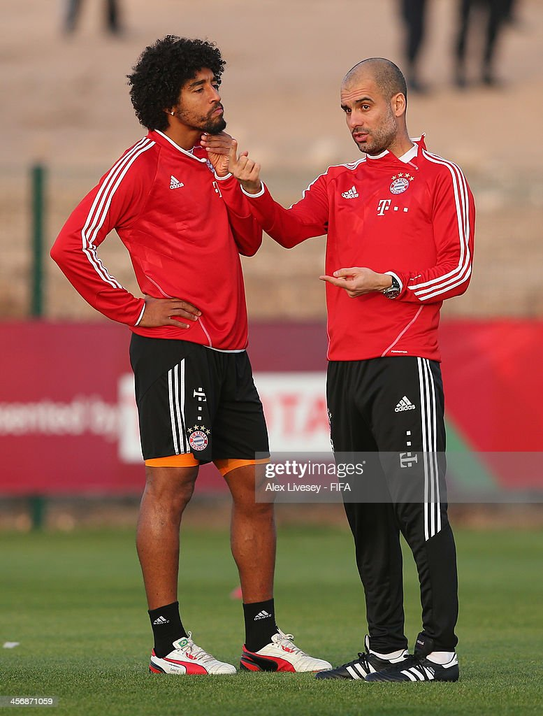 Pep Guardiola the coach of Bayern Muenchen talks with Dante during a training session at the Agadir Stadium on December 15, 2013 in Agadir, Morocco.