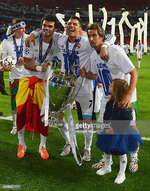 Pepe Cristiano Ronaldo and Fabio Coentrao of Real Madrid celebrate with the Champions League trophy during the UEFA Champions League Final between...
