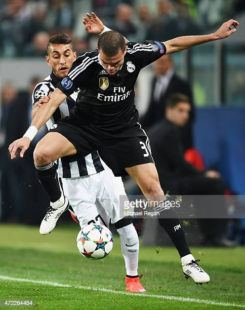 Pepe of Real Madrid CF battles with Roberto Pereyra of Juventus during the UEFA Champions League semi final first leg match between Juventus and Real...