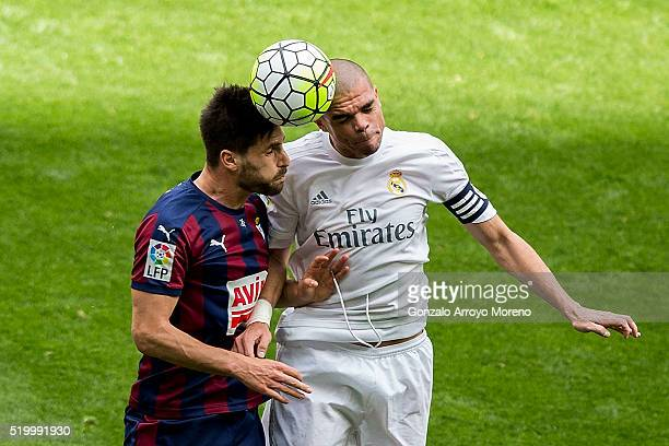 Pepe of Real Madrid CF wins the header before Adrian Gonzalez of SD Eibar during the La Liga match between Real Madrid CF and SD Eibar at Estadio...