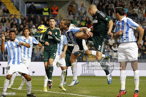 Pepe of Real Madrid competes for the ball with Ignacio Camacho of Malaga during the La Liga match between Malaga CF and Real Madrid at La Rosaleda...