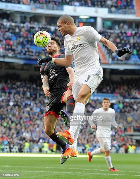 Pepe of Real Madrid heads the ball beside Hugo Mallo of Celta Vigo during the La Liga match between Real Madrid CF and Celta Vigo at Estadio Santiago...