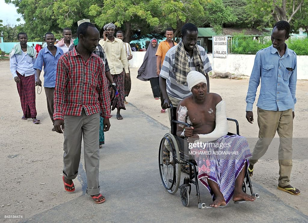 Pepole help a wounded man on June 26, 2016 the day after a terror attack on a hotel in the Somali capital Mogadishu that killed at least 11 people and was claimed by Al-Qaeda-affiliated al-Shabab militants. At least 11 people were killed on June 25, 2016 in an attack on a hotel in the Somali capital Mogadishu that was swiftly claimed by Al-Qaeda-affiliated Shabaab militants. The assault, the latest in a series by the Islamist group targeting hotels and restaurants, began when a suicide bomber detonated a car laden with explosives outside the building. / AFP / MOHAMED
