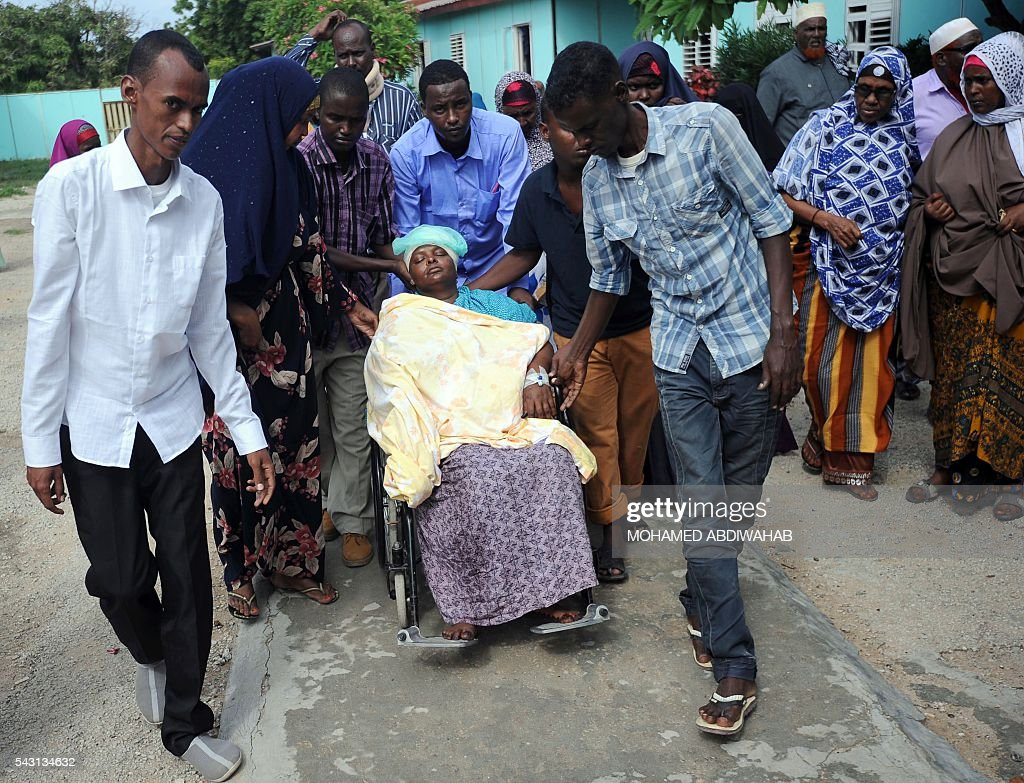Pepole help a wounded woman on June 26, 2016 the day after a terror attack on a hotel in the Somali capital Mogadishu that killed at least 11 people and was claimed by Al-Qaeda-affiliated al-Shabab militants. At least 11 people were killed on June 25, 2016 in an attack on a hotel in the Somali capital Mogadishu that was swiftly claimed by Al-Qaeda-affiliated Shabaab militants. The assault, the latest in a series by the Islamist group targeting hotels and restaurants, began when a suicide bomber detonated a car laden with explosives outside the building. / AFP / MOHAMED
