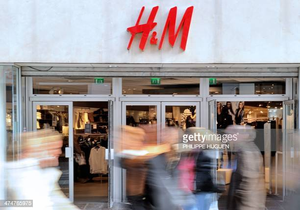 Pepole walk in front of the entrance of a HM clothing store on February 24 2014 shows in the French northern city of Lille AFP PHOTO / PHILIPPE HUGUEN