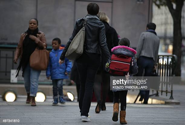 Pepople and children are pictured at a metro station on their way to school and work early on November 16 2015 in Paris three days after the...