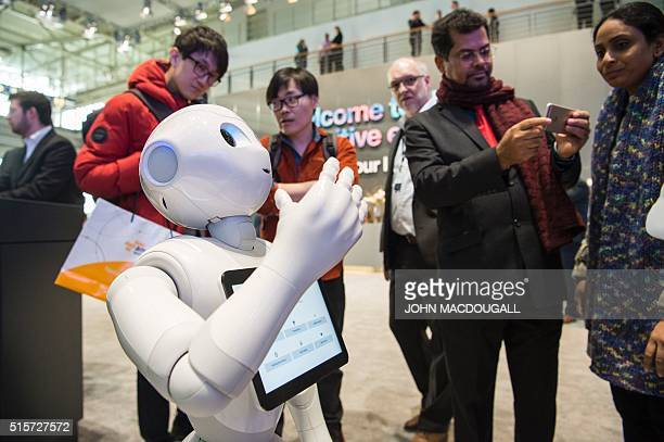 Pepper an interactive robot from IBM's Watson AI department engages with fairgoers at the Digital Business fair CEBIT in Hanover central Germany on...