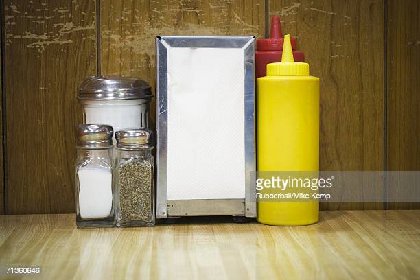 Pepper shaker and salt shaker with a napkin holder on a table in a restaurant