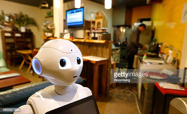 Pepper the humanoid robot manufactured by SoftBank Group Corp stands in a karaoke bar as owner Masahiko Yoshida rear cooks in the kitchen in Yokohama...