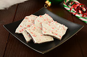 A plate of peppermint bark with candy canes and Christmas decorations