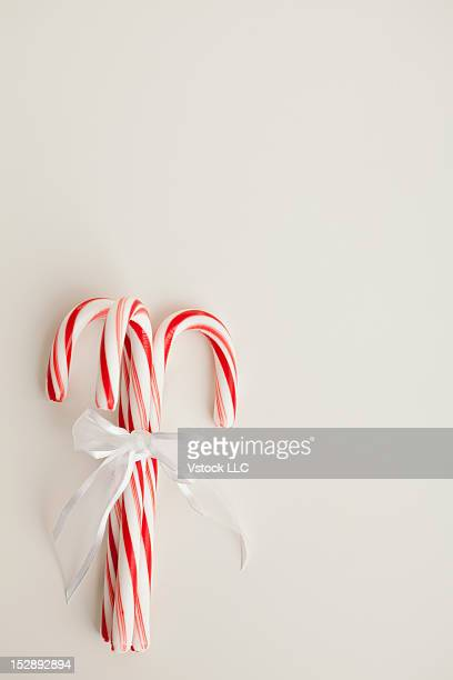 Peppermint candy canes tied with white ribbon on white background