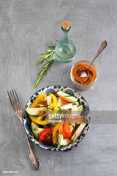 Peppers and courgette salad with rosemary, chili powder and a bottle of vinegar