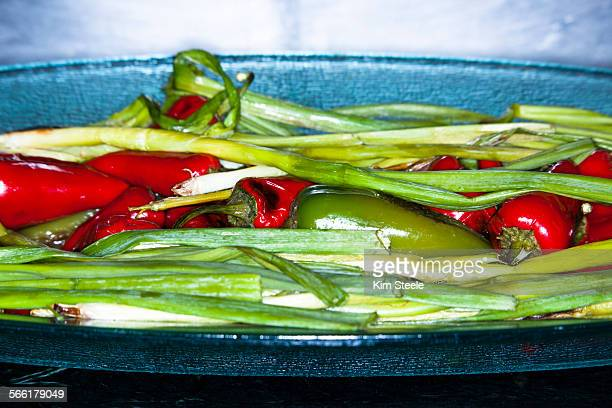 Peppers and green onions on plate in restaurant