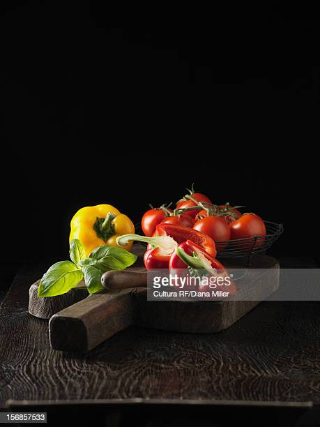 Peppers tomatoes and basil on board