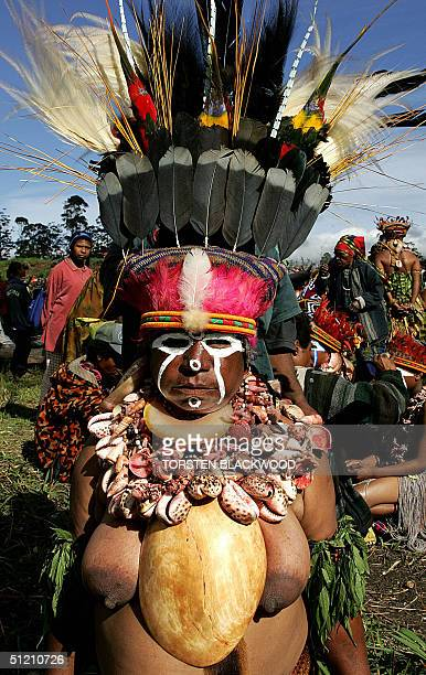 Pepre woman adorned in birdofparadise plumes and wearing a giant bailer shell waits to perform at the annual singsing cultural festival in Mount...