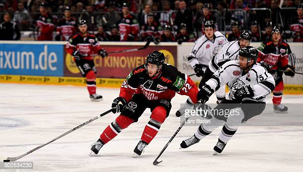 Per Aslund of Koeln is challenged by Marcus Weber of Nuernberg during the DEL match between Koelner Haie and Thomas Sabo Ice Tigers at Lanxess Arena...
