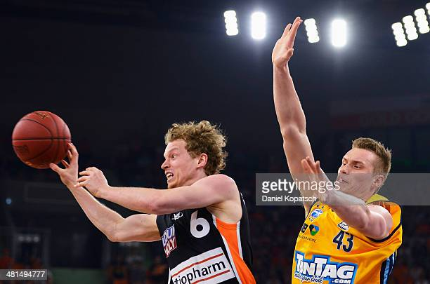 Per Guenther of Ulm is challenged by Leon Radosevic of Berlin during the Beko BBL Top Four final match between Alba Berlin and ratiopharm Ulm at...
