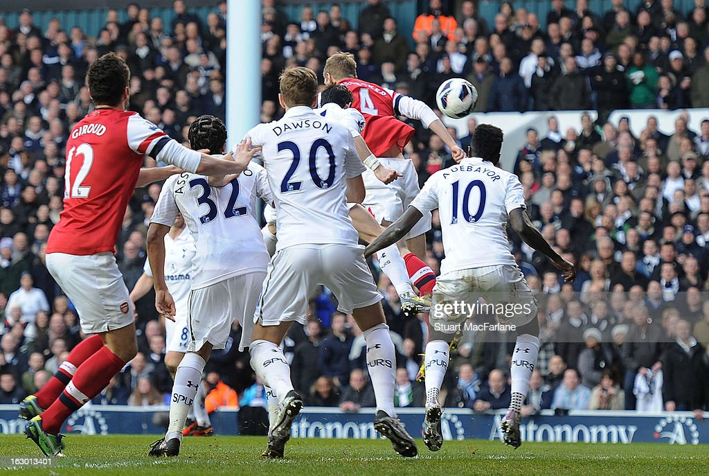 Per Meretesacker (4) heads past Tottenham's <a gi-track='captionPersonalityLinkClicked' href=/galleries/search?phrase=Emmanuel+Adebayor&family=editorial&specificpeople=484018 ng-click='$event.stopPropagation()'>Emmanuel Adebayor</a> to score the Arsenal goal during the Barclays Premier League match between Tottenham Hotspur and Arsenal at White Hart Lane on March 3, 2013 in London, England.