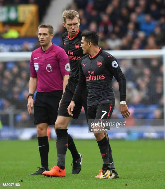 Per Mertesacker and Alexis Sanchez of Arsenal during the Premier League match between Everton and Arsenal at Goodison Park on October 22 2017 in...