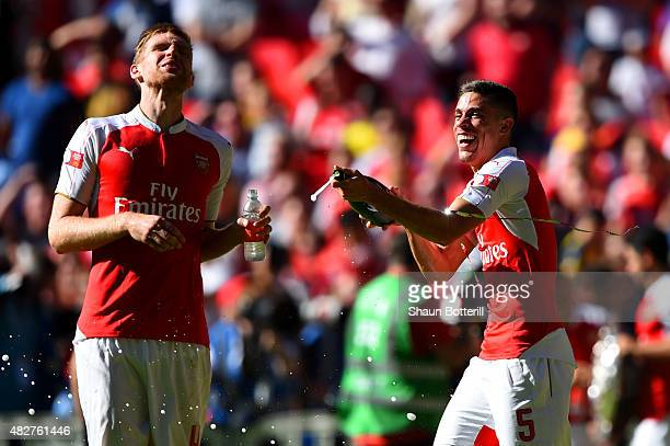 Per Mertesacker and Gabriel of Arsenal celebrate their 10 win in the FA Community Shield match between Chelsea and Arsenal at Wembley Stadium on...