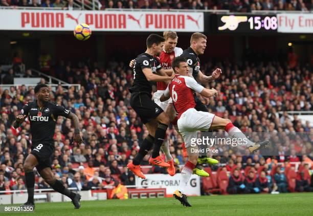 Per Mertesacker and Laurent Koscielny of Arsenal challenge Federico Fernandez and Alfie Mawson of Swansea during the Premier League match between...