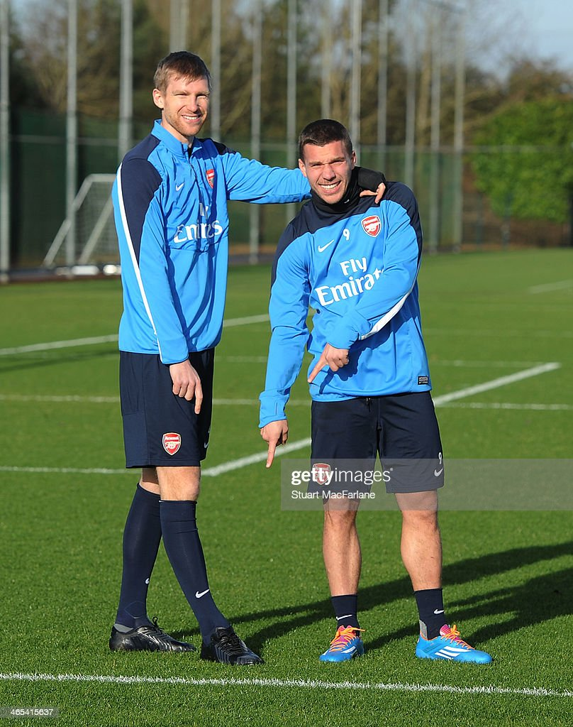 Per Mertesacker and Lukas Podolski of Arsenal during a training session at London Colney on January 27, 2014 in St Albans, England.
