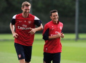 Per Mertesacker and Mesut Oezil of Arsenal during a training session at London Colney on September 12 2013 in St Albans England