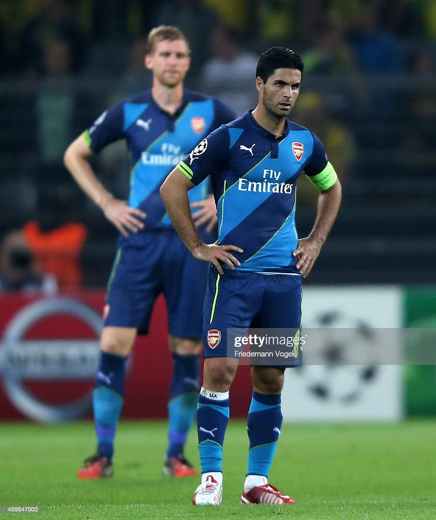 Per Mertesacker and Mikel Arteta of Arsenal looks dejected during the UEFA Champions League Group D match between Borussia Dortmund and Arsenal at Signal Iduna Park on September 16, 2014 in Dortmund, Germany.