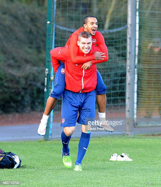 Per Mertesacker and Theo Walcott of Arsenal before the Arsenal Training Session at London Colney on December 20 2014 in St Albans England