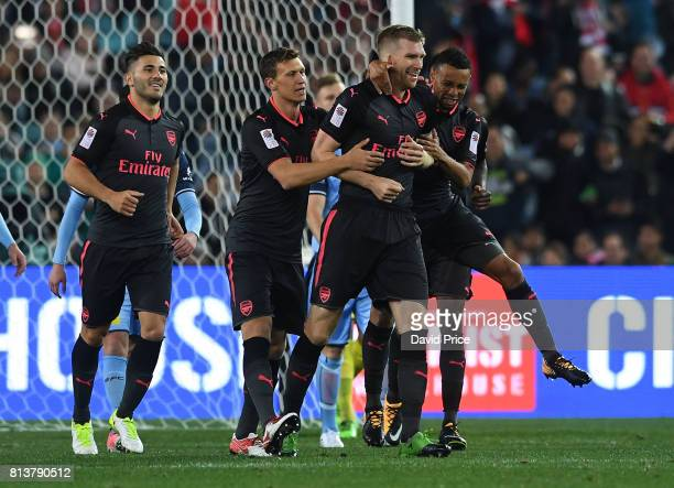 Per Mertesacker celebrates scoring a goal for Arsenal with Sead Kolasinac Krystian Bielik and Francis Coquelin during the match between Sydney FC and...