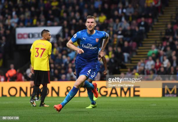 Per Mertesacker celebrates scoring for Arsenal during the Premier League match between Watford and Arsenal at Vicarage Road on October 14 2017 in...