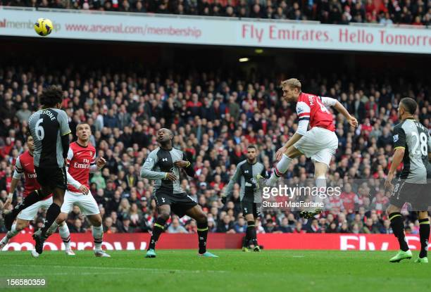 Per Mertesacker heads past Tottenham goalkeeper Hugo Lloris to score the 1st Arsenal goal during the Barclays Premier League match between Arsenal...
