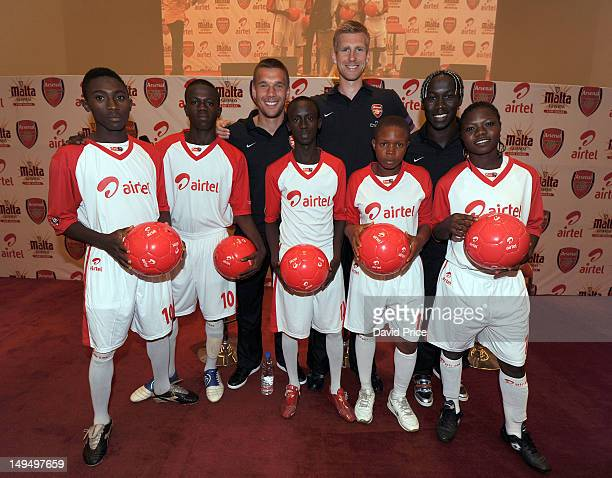 Per Mertesacker Lukas Podolski and Bacary Sagna of Arsenal FC pose with fans at an Arsenal Fans Party at the Eko Hotel on July 29 2012 in Lagos...