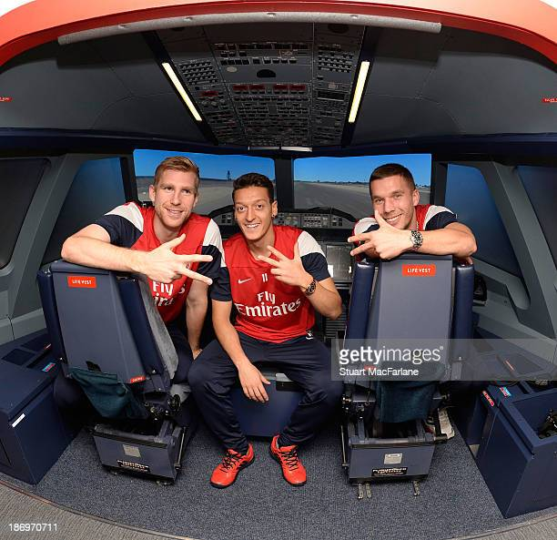 Per Mertesacker Mesut Oezil and Lukas Podolski of Arsenal pose in the Emirates' A380 flight simulator on October 31 2013 in Greenwich England