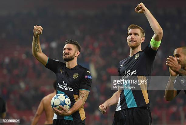 Per Mertesacker of Arsenal and Olivier Giroud of Arsenal celebrate at the end of Arsenal's win in the UEFA Champions League Group F match between...