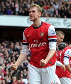 Per Mertesacker of Arsenal celebrates after scoring his team's first goal to equalise during the Barclays Premier League match between Arsenal and...