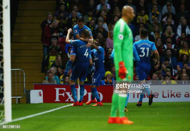 Per Mertesacker of Arsenal celebrates scoring his sides first goal with team mates during the Premier League match between Watford and Arsenal at...