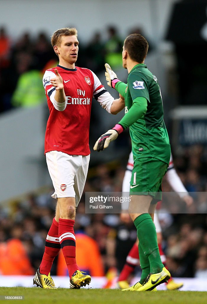 Per Mertesacker of Arsenal celebrates with his goalkeeper Wojciech Szczesny after scoring his team's first goal during the Barclays Premier League match between Tottenham Hotspur and Arsenal FC at White Hart Lane on March 3, 2013 in London, England.