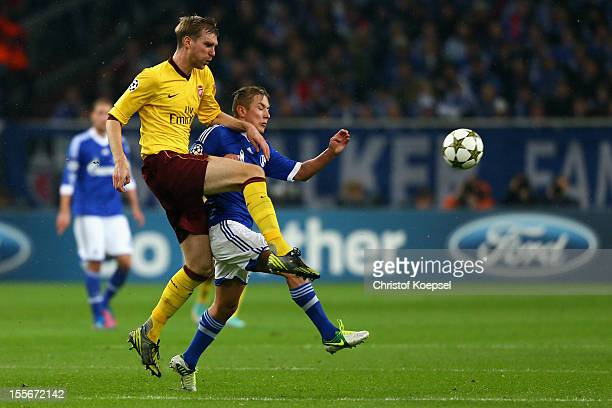 Per Mertesacker of Arsenal challenges Lewis Holtby of Schalke during the UEFA Champions League group B match between FC Schalke 04 and Arsenal FC at...