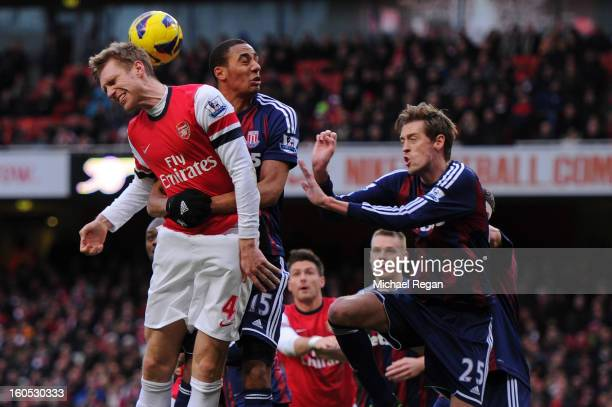 Per Mertesacker of Arsenal competes for the ball against Steven N'Zonzi and Peter Crouch of Stoke City during the Barclays Premier League match...