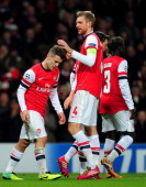 Per Mertesacker of Arsenal congratulates Jack Wilshere of Arsenal on scoring his second goal during the UEFA Champions League Group F match between...