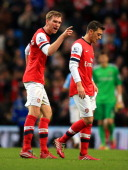 Per Mertesacker of Arsenal has words with Mesut Oezil of Arsenal during the Barclays Premier League match between Manchester City and Arsenal at...