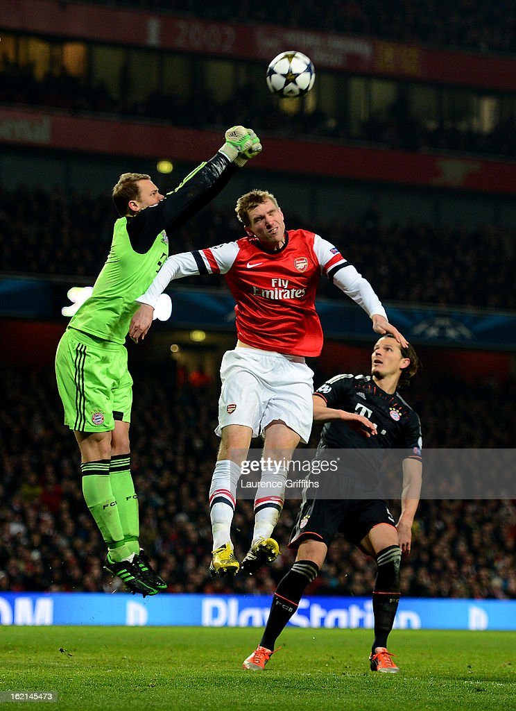 Per Mertesacker of Arsenal in action against Manuel Neuer and Daniel Van Buyten of Bayern Muenchen during the UEFA Champions League round of 16 first leg match between Arsenal and Bayern Muenchen at Emirates Stadium on February 19, 2013 in London, England.