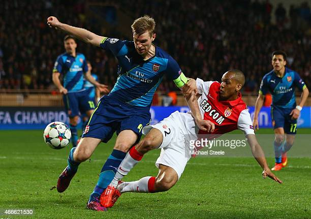 Per Mertesacker of Arsenal is challenged by Fabinho Tavares of Monaco during the UEFA Champions League round of 16 second leg match between AS Monaco...