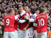 Per Mertesacker of Arsenal is congratulated by teammates Theo Walcott Lukas Podolski Oilivier Giroud Bacary Sagna and Jack Wilshere after scoring...