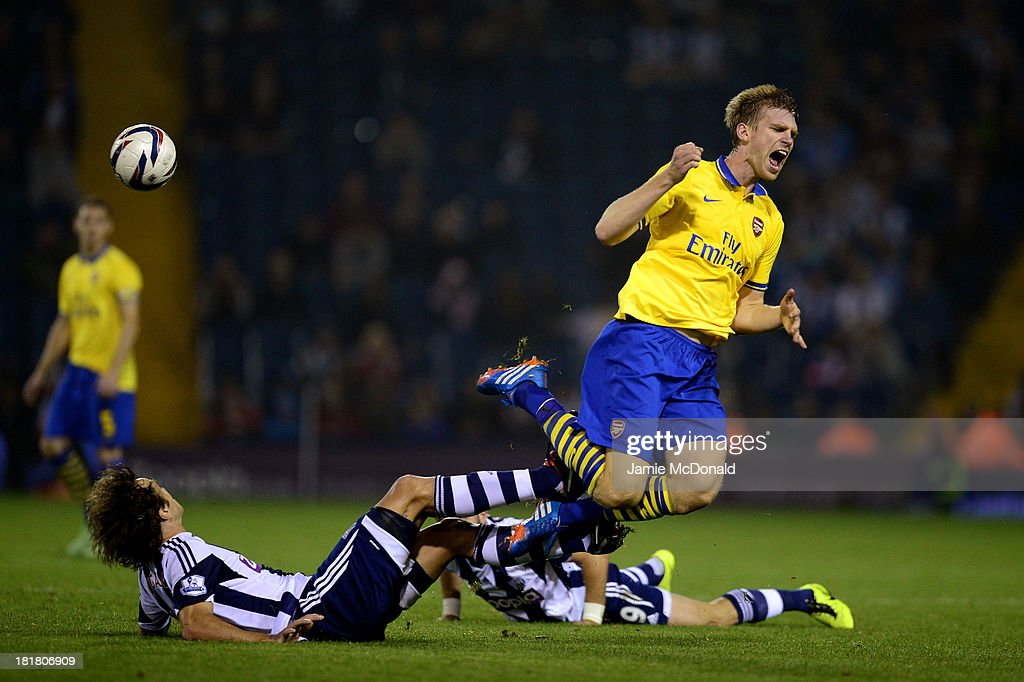 Per Mertesacker of Arsenal is tackled by Diego Lugano of West Bromwich Albion during the Capital One Cup third round match between West Bromwich...