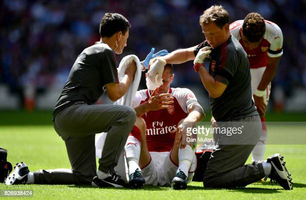 Per Mertesacker of Arsenal receives treatment from the medical team during the The FA Community Shield final between Chelsea and Arsenal at Wembley...