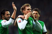 Per Mertesacker of Bremen celebrates with his team mates after scoring his team's opening goal during the Bundesliga match between Werder Bremen and...
