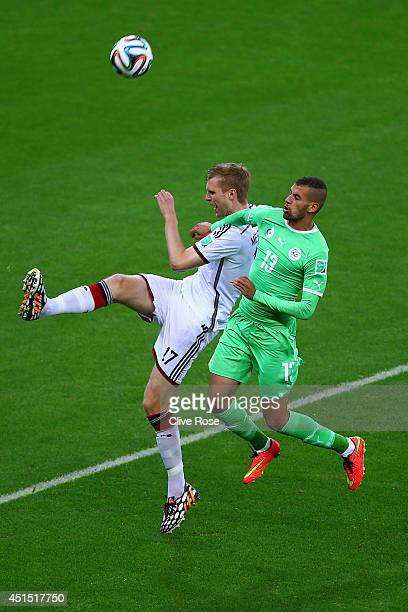 Per Mertesacker of Germany and Islam Slimani of Algeria go up for a header during the 2014 FIFA World Cup Brazil Round of 16 match between Germany...