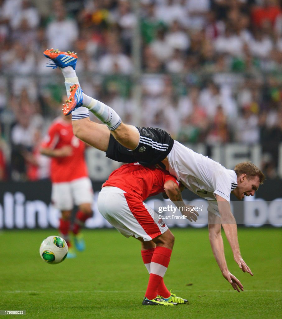 <a gi-track='captionPersonalityLinkClicked' href=/galleries/search?phrase=Per+Mertesacker&family=editorial&specificpeople=207135 ng-click='$event.stopPropagation()'>Per Mertesacker</a> of Germany challenges for the ball with <a gi-track='captionPersonalityLinkClicked' href=/galleries/search?phrase=Martin+Harnik&family=editorial&specificpeople=733193 ng-click='$event.stopPropagation()'>Martin Harnik</a> of Austria during the FIFA 2014 world cup qualifier match between Germany and Austria at the Allianz Arena on September 6, 2013 in Munich, Germany.